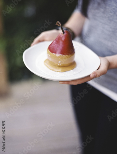 A woman holding a plate with a dessert of fresh organic pear dipped in fudge sauce.