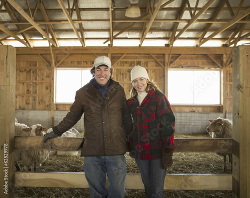 An Organic Farm in Winter in Cold Spring, New York State. A farmer and a woman standing by a pen full of sheep.