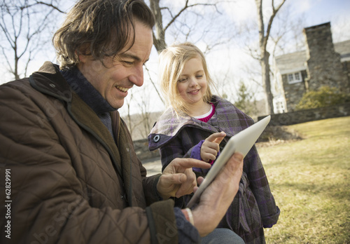 An Organic Farm in Winter in Cold Spring, New York State.  A man holding a digital tablet in his hands, showing his child the screen.
