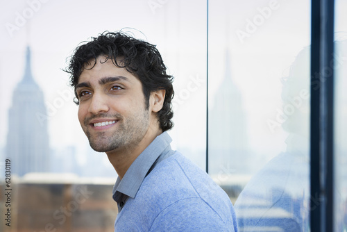 Urban Lifestyle. A young man with black curly hair wearing a blue shirt in the lobby of a building.