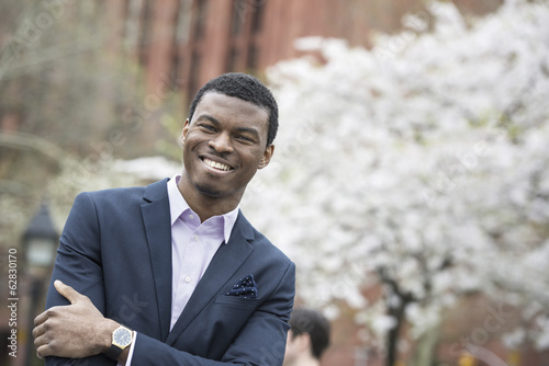 City life in spring. A man in a blue suit with arms folded, in a city park.