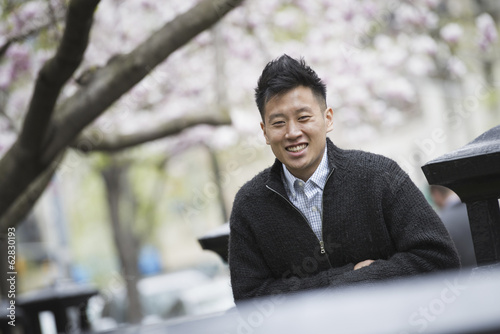 City life in spring. A young man outdoors in a city park. Sitting on a bench.