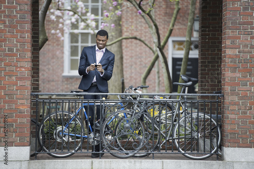 City life in spring. Young people outdoors in a city park. A man in a suit, beside a bicycle park on a sidewalk. Using his smart phone.