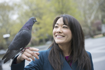 A young woman in the park with a pigeon perched on her wrist.
