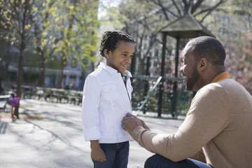 A New York city park in the spring. Sunshine and cherry blossom. A father kneeling and buttoning his son's jacket.