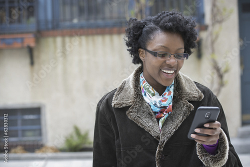A woman wearing glasses, looking at her smart phone, keeping in touch while on the go.