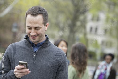 A group of people in a city park. A man in a grey sweater, checking his phone.