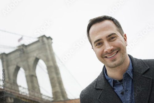 New York city, the Brooklyn Bridge crossing over the East River. A man looking at the camera and smiling.