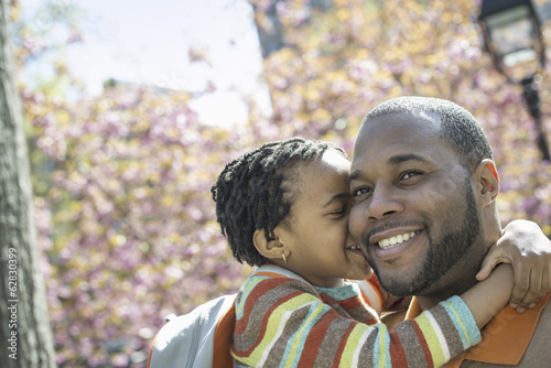 A New York city park in the spring. Sunshine and cherry blossom. A father and son in the park hugging.