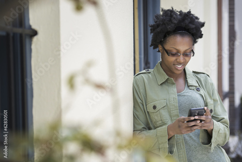 Outdoors in the city in spring. An urban lifestyle.  A woman leaning against a doorframe, checking her phone.