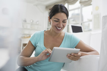 Business people. The office in summer. A young woman sitting comfortably in a quiet airy office environment. Using a digital tablet.