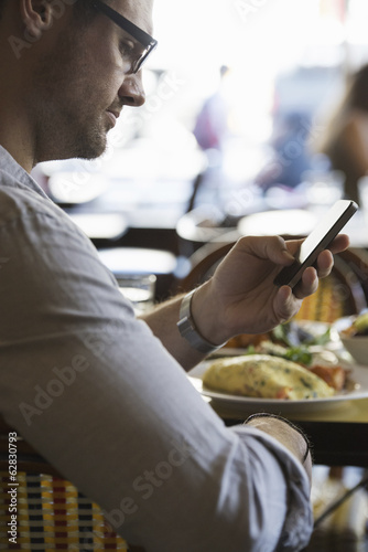 Keeping in touch on the move.  A man in casual clothes seated at a cafe table checking his smart phone.