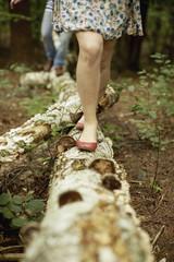 Two people walking along a fallen tree trunk in the woods.