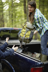 A young woman unloading rucksacks from the back of a pickup truck.
