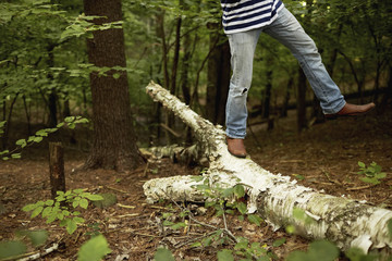 A man walking along a fallen tree trunk in the woods, balancing with one leg raised in the air.