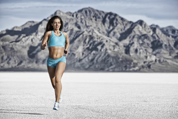 A young woman running through the landscape on the salt flats surface near Salt Lake city.