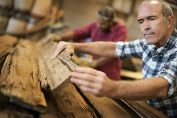 A reclaimed lumber workshop. A group of people working. A man measuring and checking planks of wood for re-use and recycling.