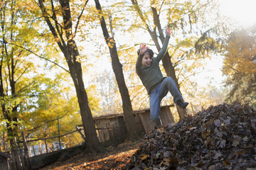 A child in autumn sunshine in a woodland. Leaping into a large pile of raked up autumn leaves.