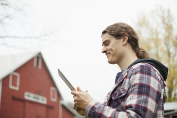 A young man using a computer tablet, a portable PC tablet device, on an organic farm.
