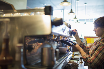 A person, barista making coffee, and frothing milk using a steam pipe, for a cappuccino. Coffee shop.