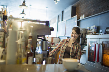 A person, barista, behind the counter at a coffee shop. A large coffee machine for making fresh coffee. A cappuccino in a white cup on the counter.