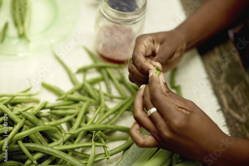 Food preparation outdoors. View onto a table, and a woman's hands preparing fresh green beans.