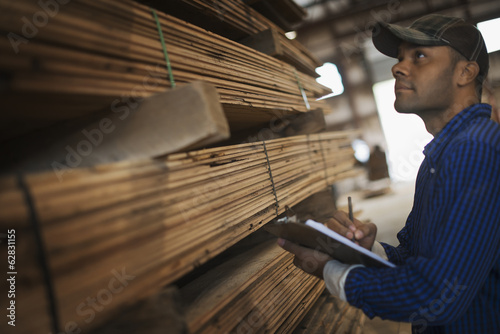 A heap of recycled reclaimed timber planks of wood. Environmentally responsible reclamation in a timber yard. A man with a clipboard by a rack of planks.