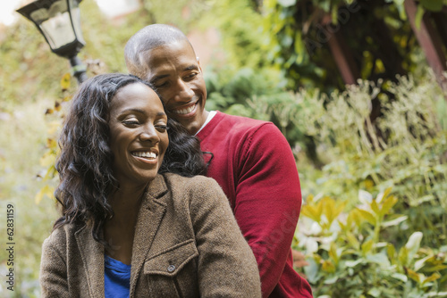 Scenes from urban life in New York City. A man and a woman, hugging each other in an garden.