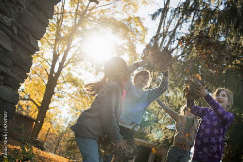 Three children in the autumn sunshine. Playing outdoors throwing the fallen leaves  in the air.