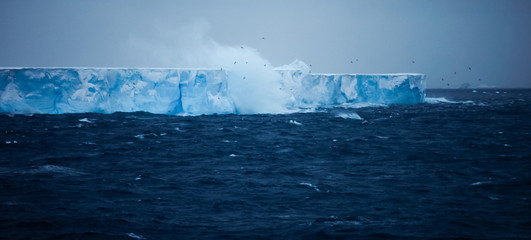 A large iceberg with steep sides, floating on the water. Waves and spray rising. Calving event.