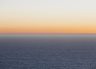 A view over the Pacific Ocean and the sunset on the horizon.