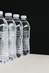 Row of clear, plastic water bottles filled with filtered water in a row. on a black background.