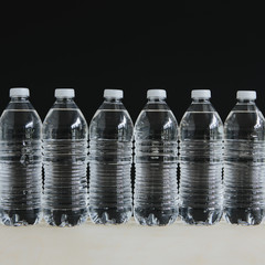 Row of clear, plastic water bottles filled with filtered water in a row, on a black background.