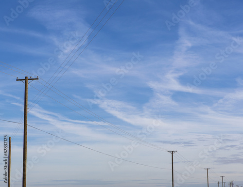 Telephone poles and power lines in a line across the landscape at Belridge, California.