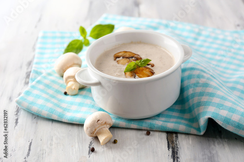 Mushroom soup in white pot, on napkin,  on wooden background