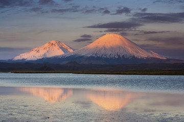 Payachata Volcanoes, twin volcanoes each standing over twenty thousand feet high, dominate the landscape in the Chilean Andes, Luaca National Park, Chile