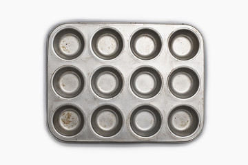 A well used, seasoned baking tray. Cookware.  A cupcake or muffin tin.