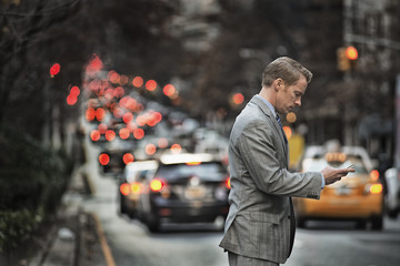 A man in a suit checking his cell phone, standing on a busy street at dusk.