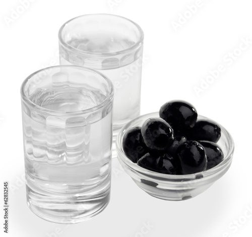 Composition with  two glasses  of vodka, and black olives,