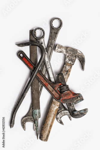 Used Tools. A group of spanners, adjustable wrench and hammer. Worn marked metal handheld tools.