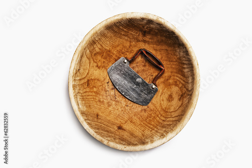 A well worn wooden chopping bowl, with a steel blade and handle.