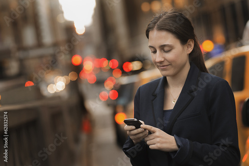 A woman in a business jacket checking her cell phone, on a city sidewalk at dusk.