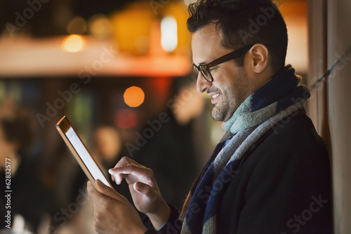 A man in a city at night, looking at a computer tablet.