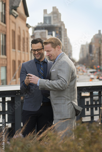 Two men in formal business clothes, standing side by side, looking at a cell phone screen or mobile phone.