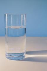 A glass of filtered water on a white surface.