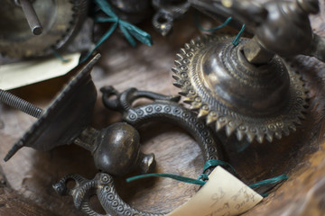 An antique store with a display of objects and furniture from the past. Chased metal decorated objects, door knocker and light fitting.