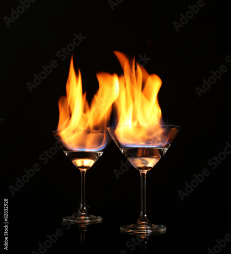Glasses with burning alcohol on black background