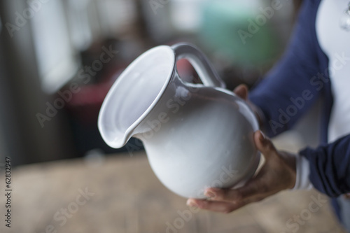 A woman holding a white pottery jug in an antique goods and furniture store.