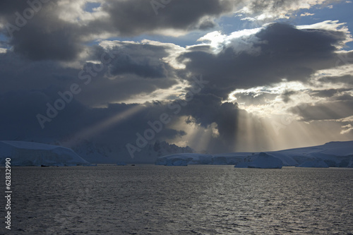 Sun breaking through the storm clouds hitting the icebergs along the west coast of the Antarctic Peninsula.