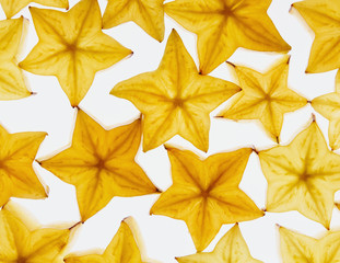 Slices of organic starfruit on a white background